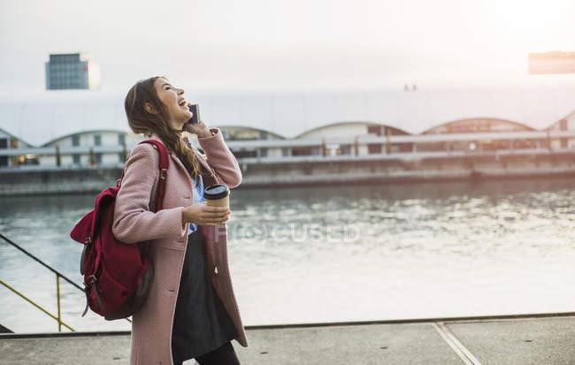 Rindo jovem mulher na beira do rio no telefone celular — Fotografia de Stock