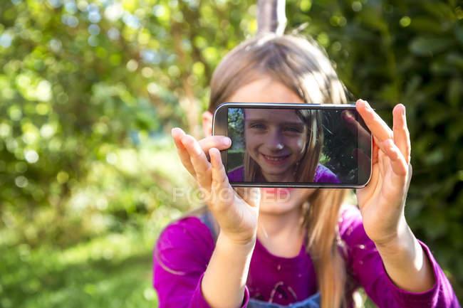 Girl zeigt Display des Smartphones mit selfie — Stockfoto