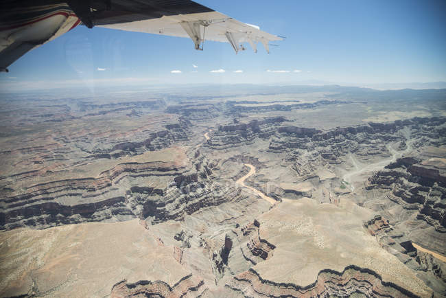 USA, Arizona, Grand Canyon, wing of airplane over rocky terrain during daytime — Stock Photo