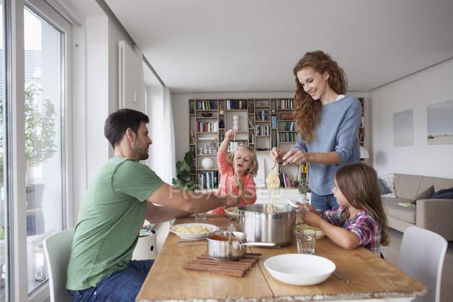 Пара с двумя детьми собираются пообедать вместе дома — стоковое фото