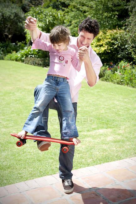 Homme jouant avec sa petite fille dans le jardin — Photo de stock