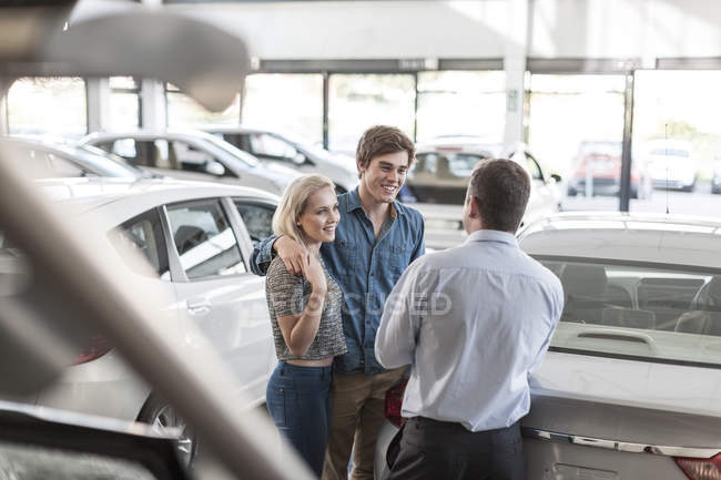 Car dealer talking to young couple in showroom — Stock Photo