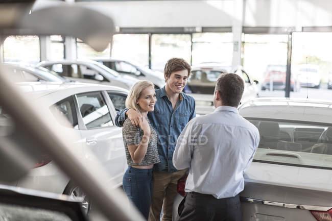 Concessionario di auto parlando con giovane coppia in showroom — Foto stock