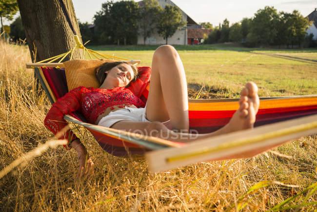 Молода жінка, відпочити в гамаку — стокове фото