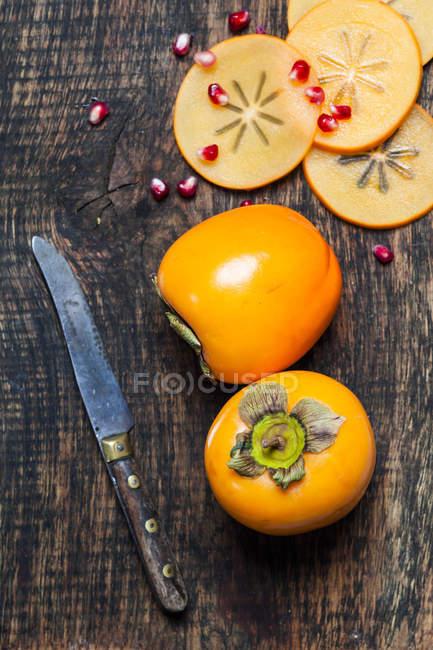 Kaki inteiro e cortado com a faca e romã sementes em madeira escura — Fotografia de Stock