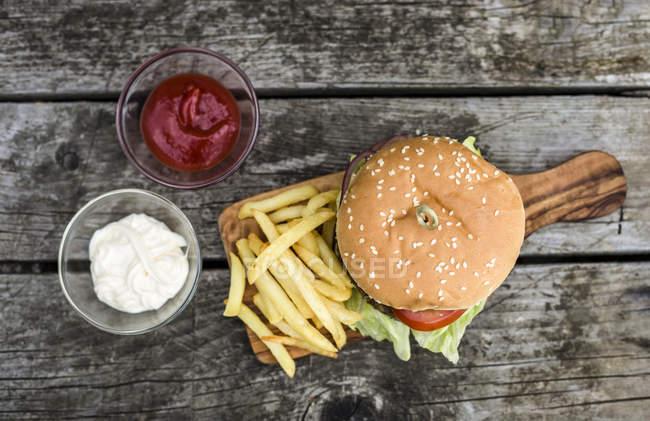 Домашний бургер с салатом, мясом, помидорами, луком и картошкой фри на доске — стоковое фото