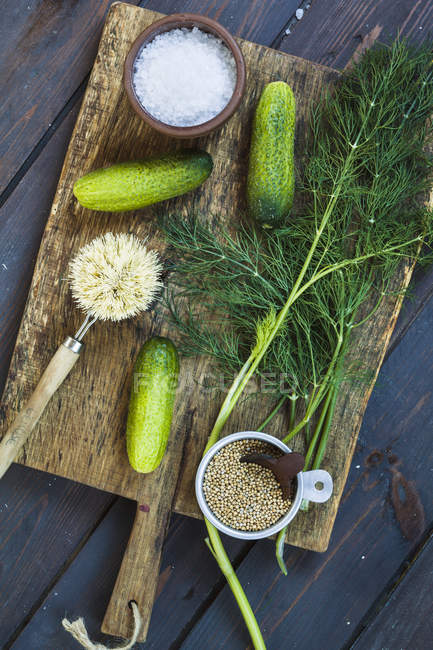Top view of gherkins, dill, salt and mustard grains on chopping board — Stock Photo