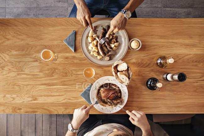 Two men in restaurant having lunch — Stock Photo