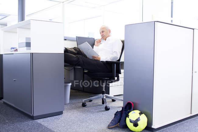 Empresário no cubículo de escritório lendo o documento — Fotografia de Stock