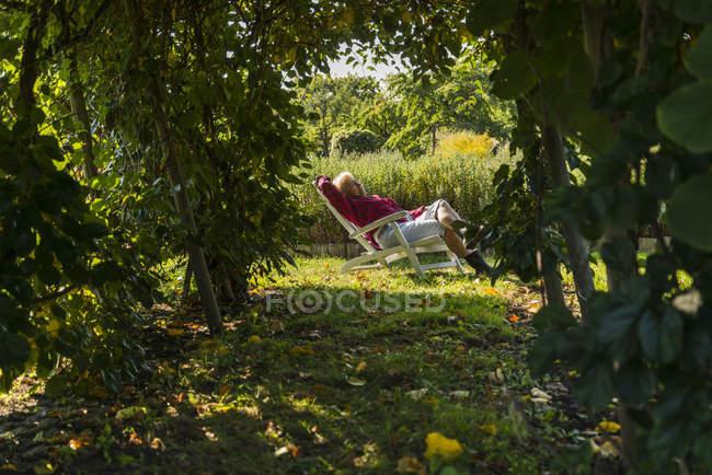 Senior woman relaxing in garden chair — Stock Photo