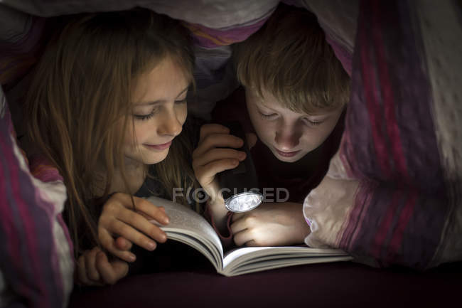Brother and sister reading book under a blanket — Stock Photo