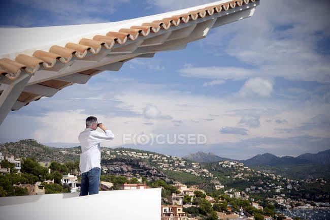 España, Mallorca, hombre de pie en la terraza de una casa mirando a la vista con binocular - foto de stock