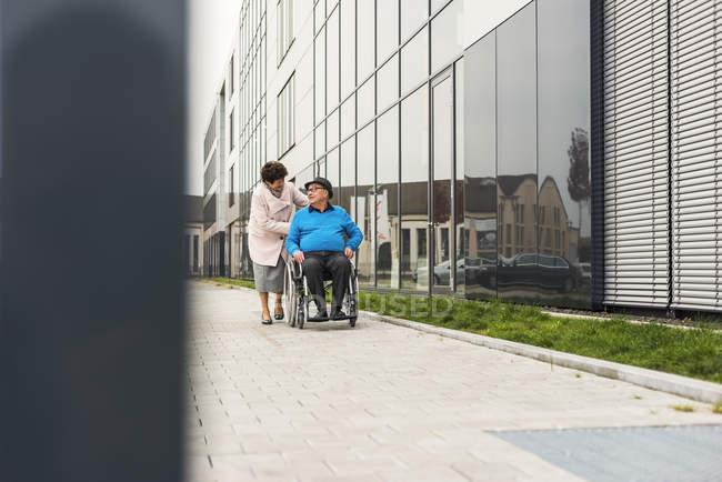Senior woman pushing husband in wheelchair on pavement — Stock Photo