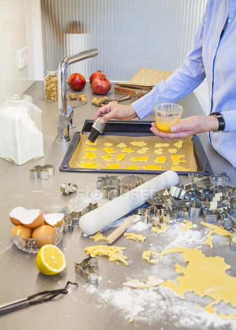 Woman spreading unbaked Christmas cookies with egg yolk — Stock Photo