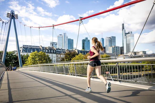Німеччина, Франкфурт, молода жінка, біг на мосту — стокове фото