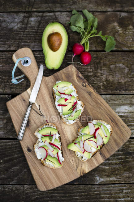Avocado radish bread on chopping board — Stock Photo