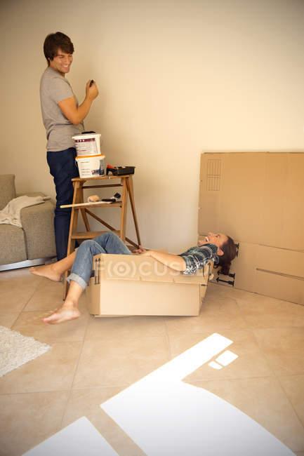 Lachende Frau im Karton mit Mann, der Wand bemalt — Stockfoto