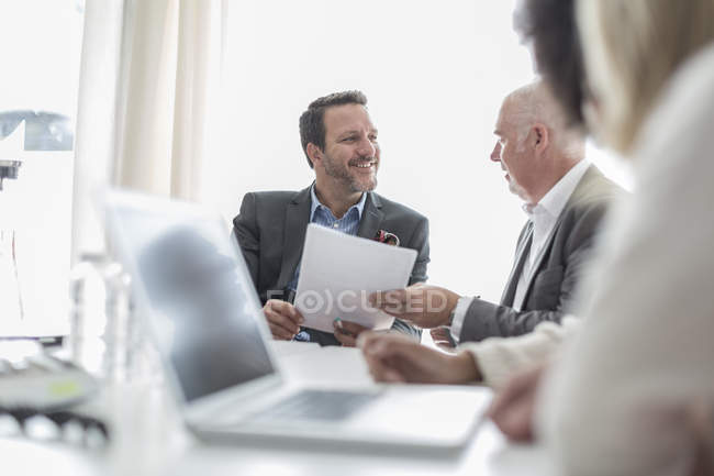 Confident business people with documents and laptop in conference room — Stock Photo