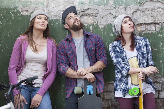 Three stylish friends with skateboards looking up — Stock Photo