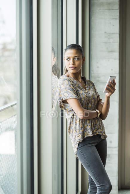 Giovane donna con il telefono cellulare che osserva dalla finestra — Foto stock