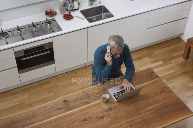 Mature man in kitchen with cell phone and laptop — Stock Photo