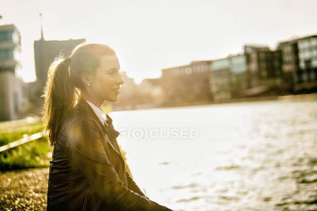Young woman relaxing at city harbour in evening twilight — Stock Photo