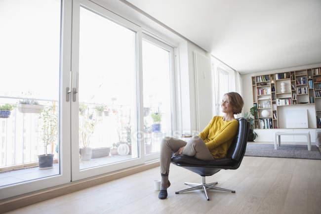 Mujer relajada en casa sentado en la silla de cuero - foto de stock