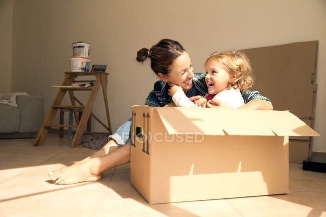 Laughing woman with daughter sitting in cardboard box — Stock Photo