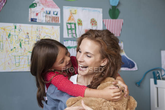Mother and little daughter having fun together in children's room — Stock Photo