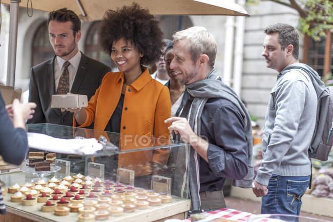 Жінка купівлі тістечка харчова ларьок у міський ринок — стокове фото