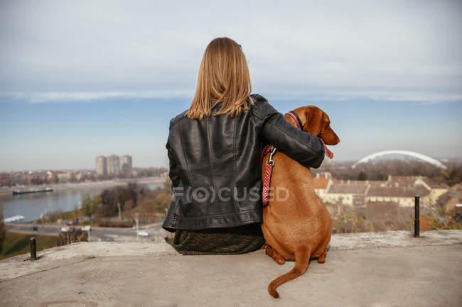 Сербия, Нови-Сад, вид сзади на молодую женщину, сидящую рядом со своей собакой и смотрящую на вид — стоковое фото