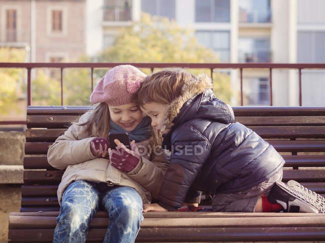 Девочка и мальчик в зимней одежде играют со смартфоном — стоковое фото