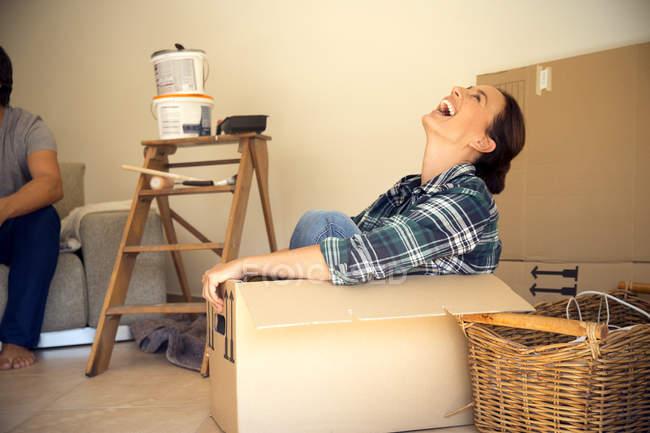 Сміється жінка в картонну коробку з чоловіком у фоновому режимі — стокове фото