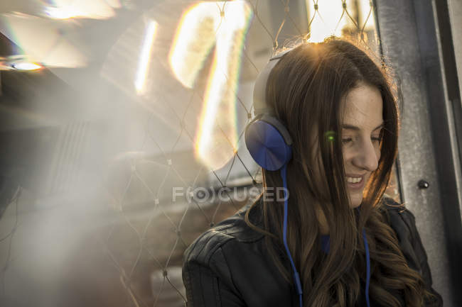 Smiling woman hearing music with headphones at backlight — Stock Photo