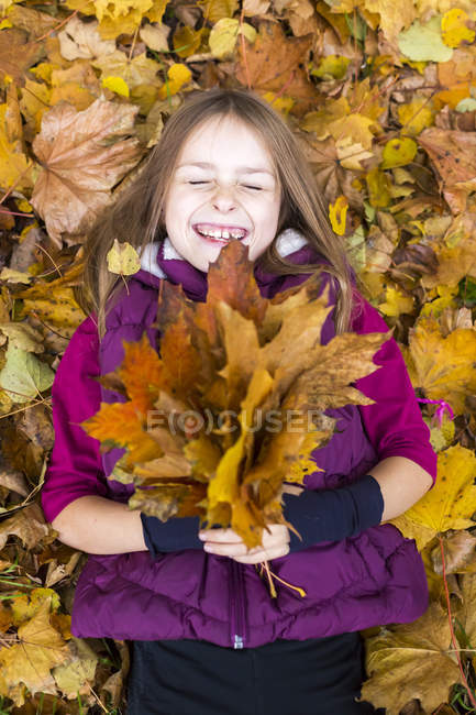 Портрет смех девушки, лежащих на земле, холдинг кучу осени листья — стоковое фото