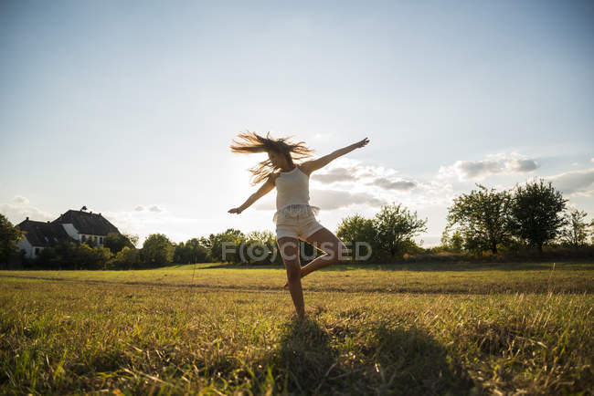 Young woman dancing on a meadow at backlight — Stock Photo