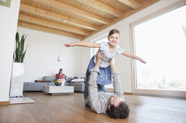 Father and daughter playing at home, pretending to fly — Stock Photo