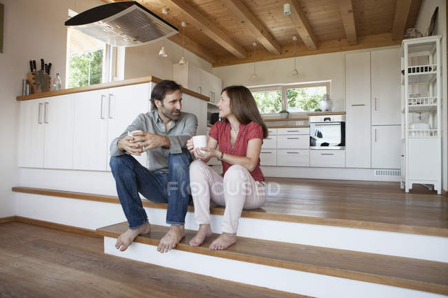 Coppia matura con coppe sedute sul pavimento a casa — Foto stock