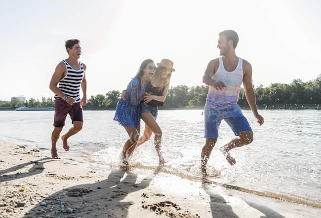Счастливые друзья бегут и смеются над рекой — стоковое фото