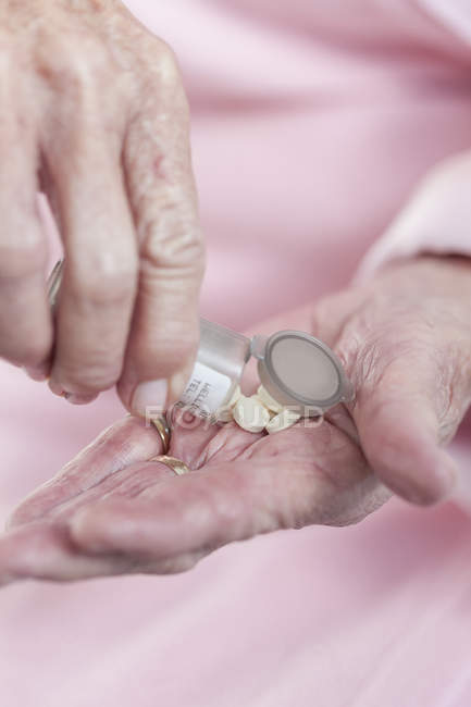 Hands of senior woman holding pills — Stock Photo