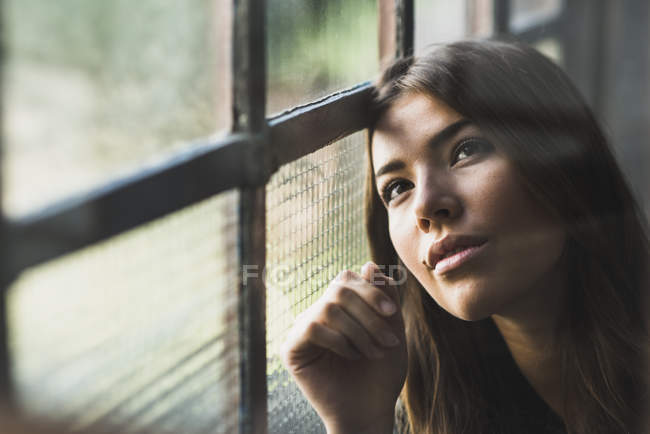 Brunette woman looking out of window — Stock Photo