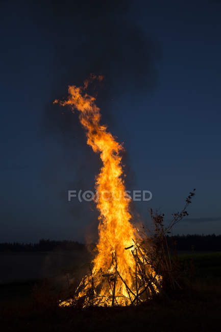 Burning camp fire on a meadow at night — Stock Photo