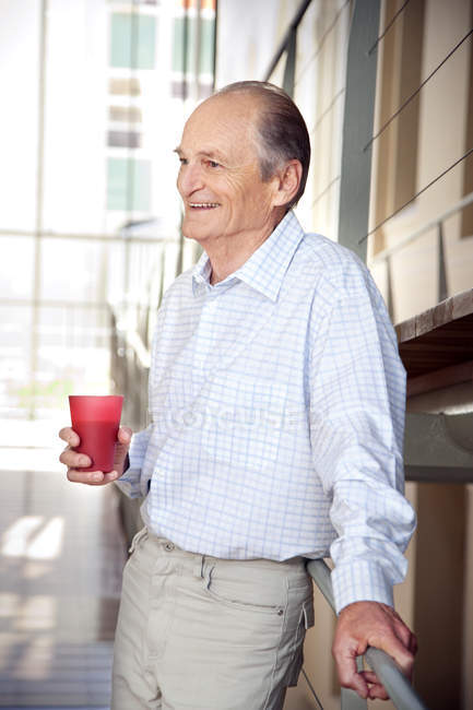 Laughing senior leaning on railing — Stock Photo
