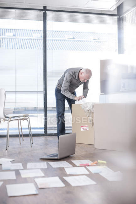 Man in new office unpacking cardboard box — Stock Photo