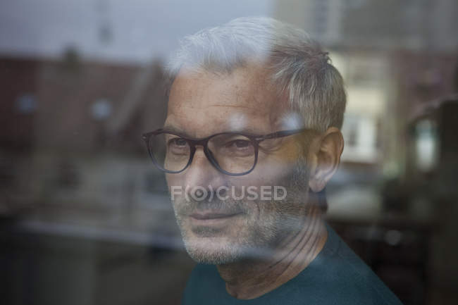 Mature man behind windowpane looking out — Stock Photo
