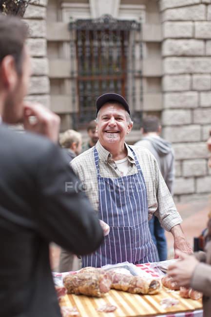 Чоловік продає ковбаски на міський ринок — стокове фото