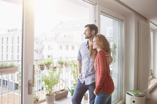 Couple looking out of window at home — Stock Photo