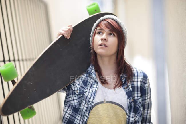 Jovem mulher segurando skate ao ar livre — Fotografia de Stock
