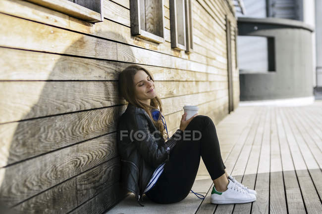 Woman with coffee by wooden wall — Stock Photo