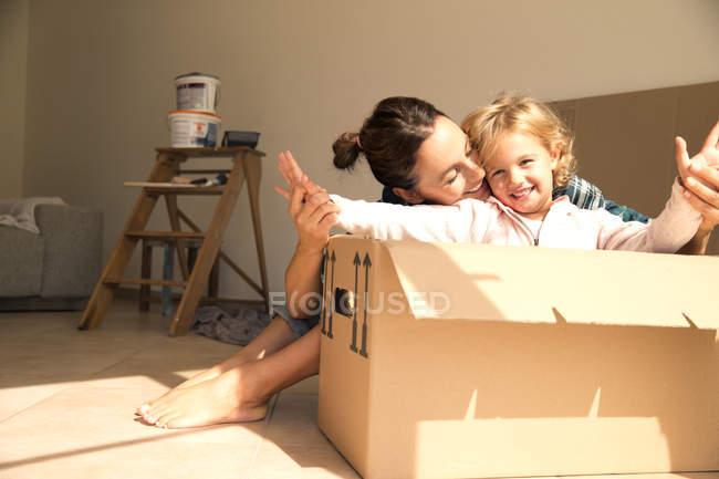 Mujer feliz con la hija sentada en caja de cartón - foto de stock